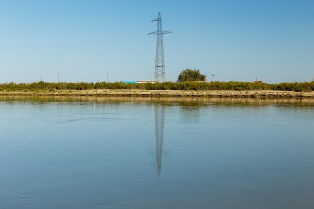 De pyloon van de machtslijn bevindt zich op de banken van de rivier van syr darya, weerspiegeld in het water, kazachstan. machtslijn kruist de rivier Premium Foto