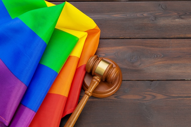 De rechterhamer van woden van wet en rechtvaardigheid met lgbtvlag in regenboogkleuren op houten achtergrond Premium Foto