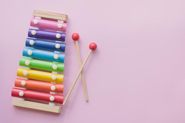 De regenboog kleurde houten xylofoon van het stuk speelgoed op roze bacground. speelgoed klokkenspel van metaal en hout. copyspace Premium Foto