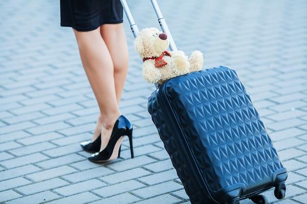 De reis, bebouwd jong toevallig wijfje gaat bij luchthaven bij venster met koffer wachtend op vliegtuig Premium Foto