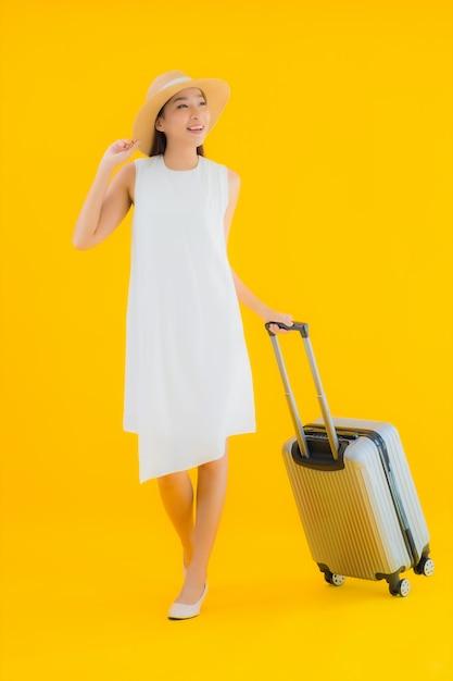 De reisconcept van de portret mooi jong aziatisch vrouw met bagage Gratis Foto