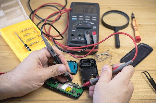 De reparatie mobiele telefoon in de werkplaats. Premium Foto