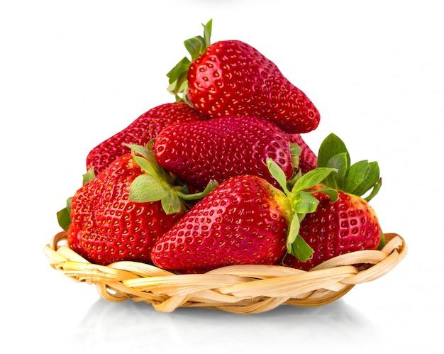 De rieten bruine mand met aardbeien die op witte achtergrond worden geïsoleerd. rijpe aardbeien close-up. Premium Foto