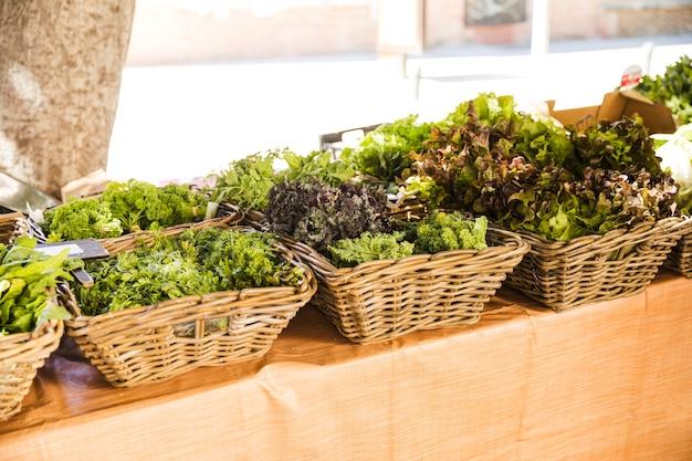 De rieten mand van verse bladgroenten schikte in rij bij marktkraam Gratis Foto