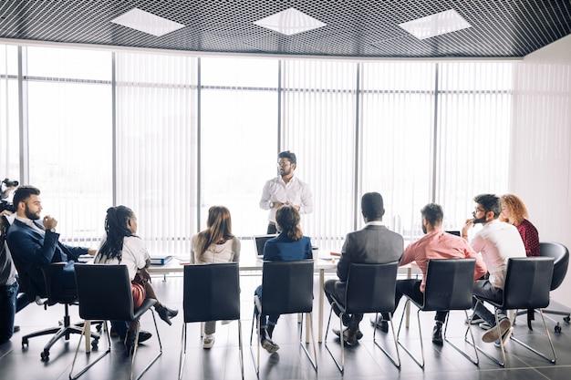 De rij van onherkenbare bedrijfsmensen zit in conferentiezaal bij bedrijfsevenement. Premium Foto