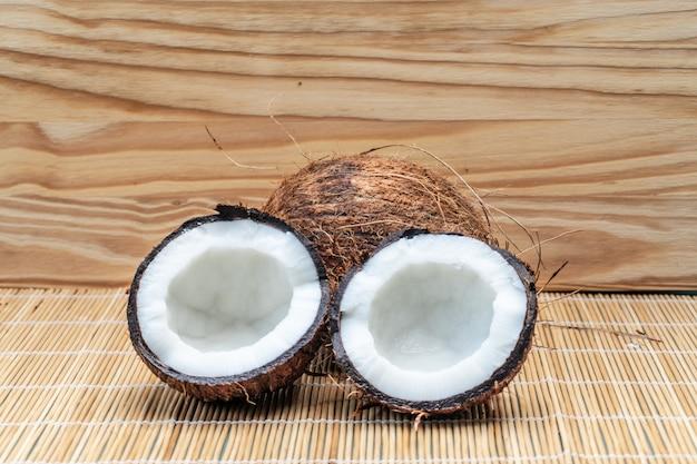 De rijpe helft sneed kokosnoot op een houten achtergrond Premium Foto
