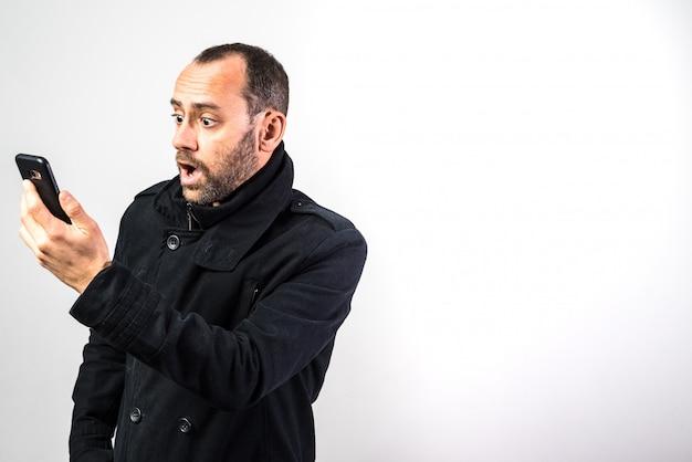De rijpe mens consulteerde zijn cellphone met verrast gezicht, gezichtsuitdrukkingen, die op witte achtergrond worden geïsoleerd. Premium Foto