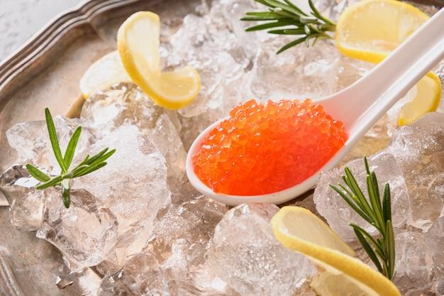 De rode kaviaar in lepel versiert citroen op ijsblokje. detailopname. Premium Foto
