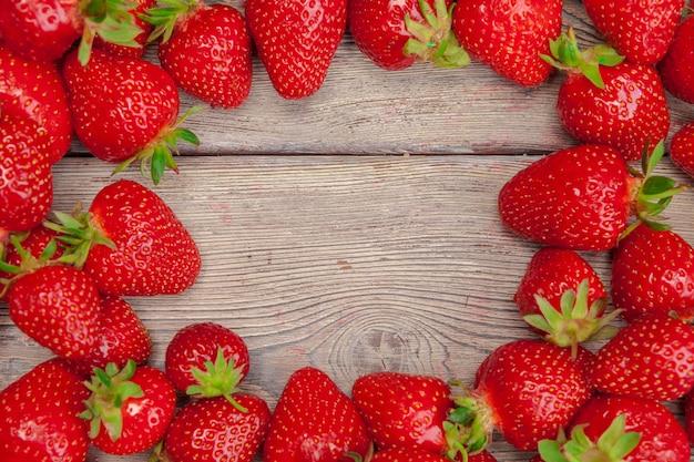 De rode rijpe aardbeien op houten lijst sluiten omhoog Premium Foto