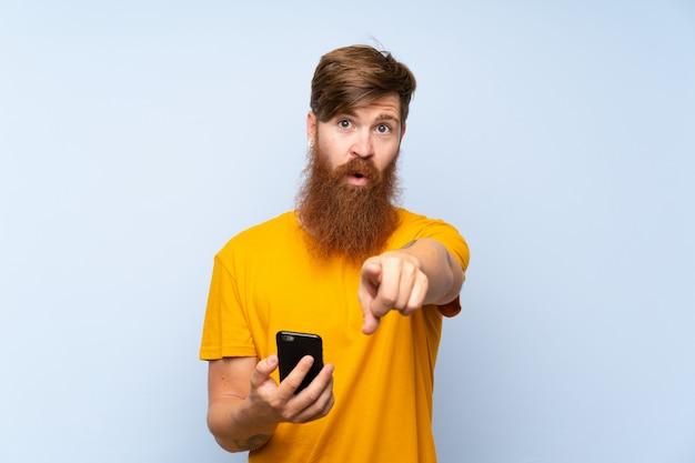 De roodharigeman met lange baard met mobiel over geïsoleerde blauwe muur richt vinger op u met een zekere uitdrukking Premium Foto