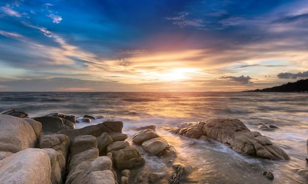 De rots en de zee in de kleur van de zonsondergang tijd. Premium Foto