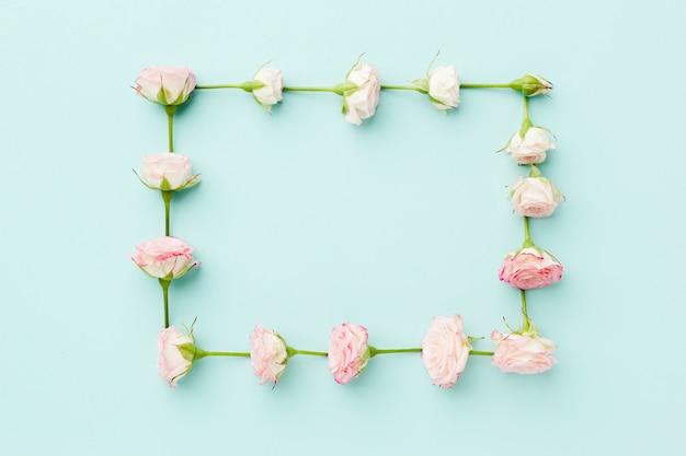 De roze vlakte van het rozenkader legt op blauwe achtergrond Gratis Foto