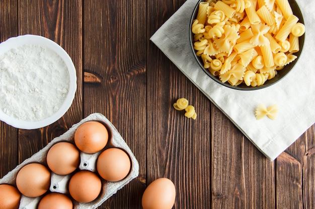 De ruwe deegwaren in een kom met eieren, meelvlakte leggen op houten en keukenhanddoek Gratis Foto
