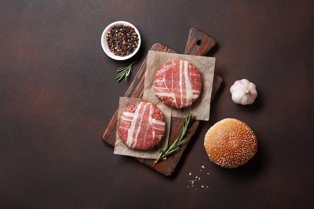 De ruwe koteletten, de sla, het broodje en de ui van hamburgeringrediënten op roestige achtergrond Premium Foto