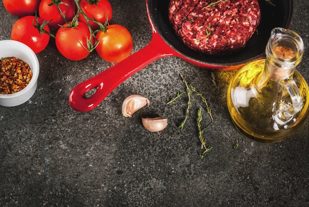 De ruwe organische koteletten van rundvleesvleesburgers met kruiden, tijm, tomaten, olijfolie in pan op zwarte, copyspace hoogste mening Premium Foto