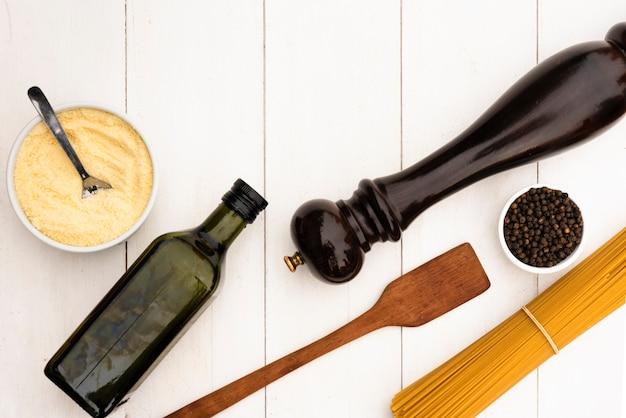 De ruwe spaghettideegwaren en het is ingrediënt met keukenwerktuig op witte lijst Gratis Foto