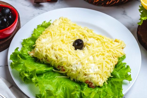 De salade van vooraanzichtmimosa op sla met zwarte olijven Gratis Foto