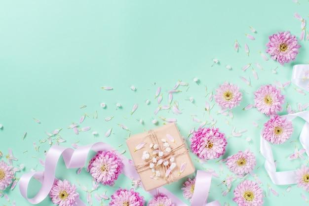 De samenstelling van bloemen met hartjes en geschenkdoos op een pastel Premium Foto