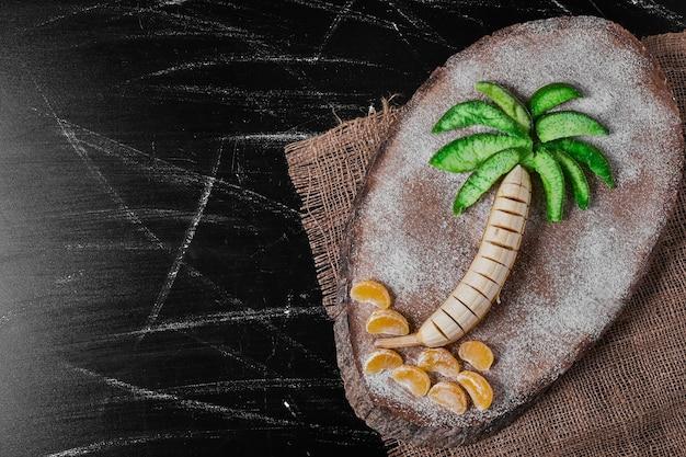 De samenstelling van het palmboomfruit op houten schotel. Gratis Foto