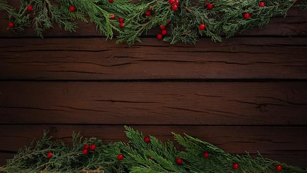 De samenstelling van pijnbomenkerstmis op een houten kaderachtergrond met exemplaarruimte Gratis Foto