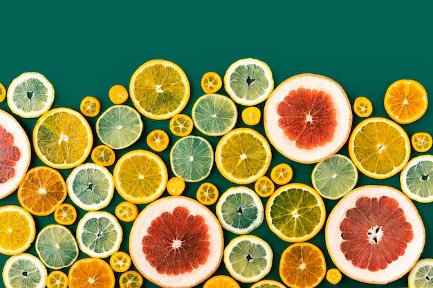 De sappige verse heldere de zomer groene achtergrond met vlakke citrusvruchten, legt. Premium Foto