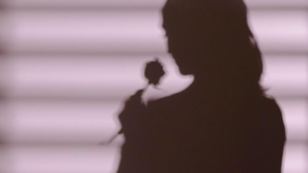 De schaduw van de vrouw met een roos Gratis Foto