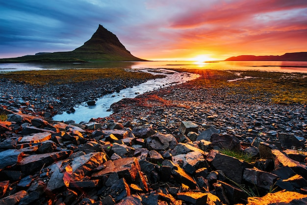 De schilderachtige zonsondergang over landschappen en watervallen. kirkjufellberg ijsland Premium Foto