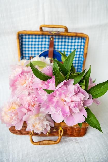 De schoonheid van een roze pioenrozenboeket in een vintage authentieke bruine koffer. Premium Foto