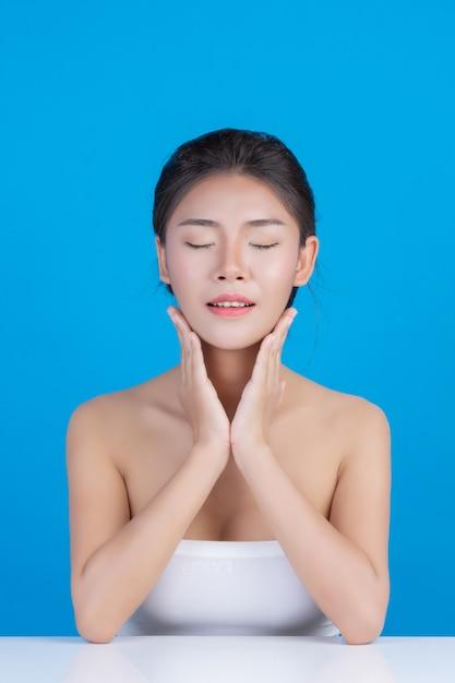 De schoonheid van vrouwen met perfecte huidgezondheidsbeelden haar gezicht aanraken en glimlachen als een spa om haar huid te verwennen blauw Gratis Foto