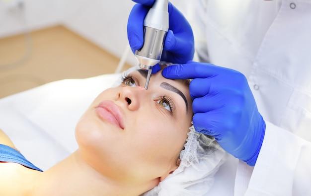 De schoonheidsspecialist verwijdert pigmentatie en vasculaire netten op de huid van de patiënt Premium Foto