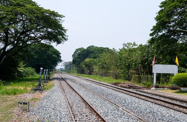 De seinpaal van het lokale treinstation voordat je de lokale weg oversteekt in de buurt van de buitenwijk. Premium Foto