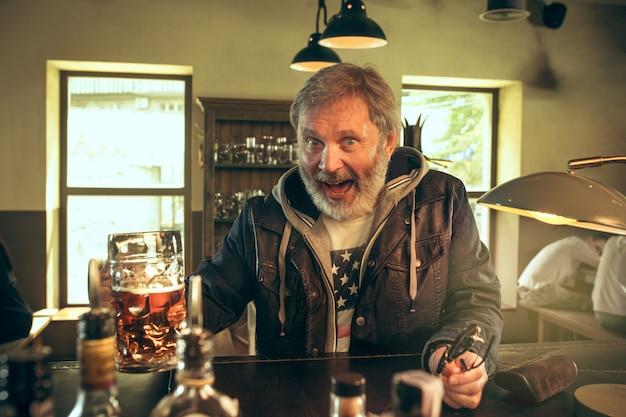 De senior bebaarde man bier drinken in pub Gratis Foto