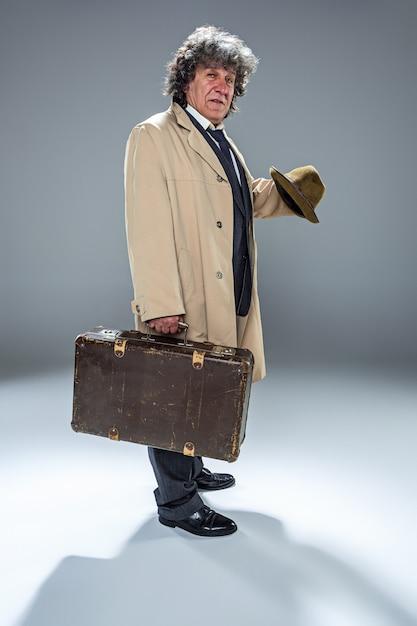 De senior man als detective of baas van maffia op grijze studio achtergrond Gratis Foto