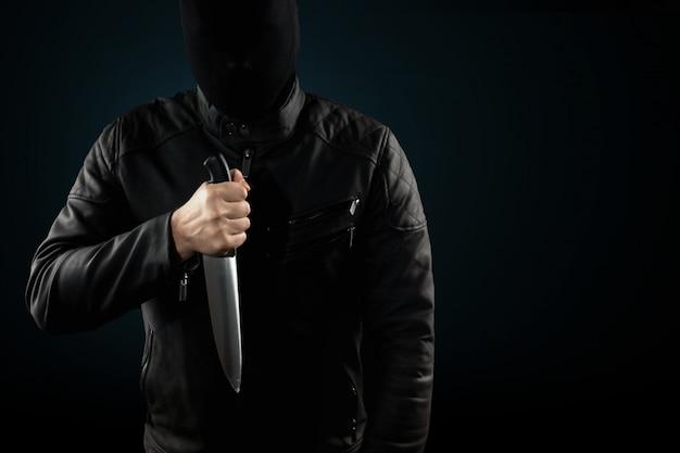 De seriemoordenaar, een maniak met een mes en een zwarte chuolkom op zijn hoofd Premium Foto