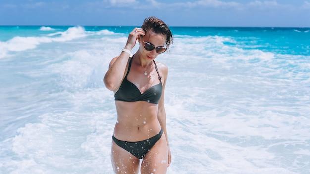 De sexy vrouw zwemt binnen slijtagebikini in het oceaanwater Gratis Foto