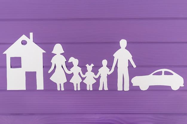 De silhouetten gesneden uit papier van man en vrouw met twee meisjes en jongen huis en auto in de buurt Premium Foto