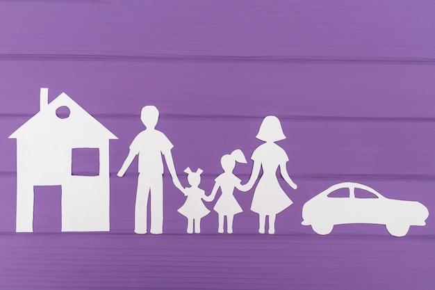 De silhouetten gesneden uit papier van man en vrouw met twee meisjes, huis en auto in de buurt Premium Foto