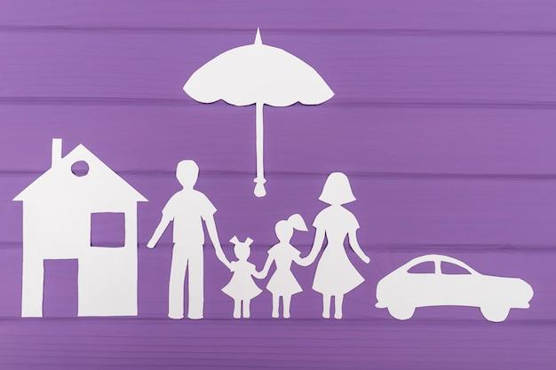 De silhouetten gesneden uit papier van man en vrouw met twee meisjes onder de paraplu, huis en auto in de buurt Premium Foto