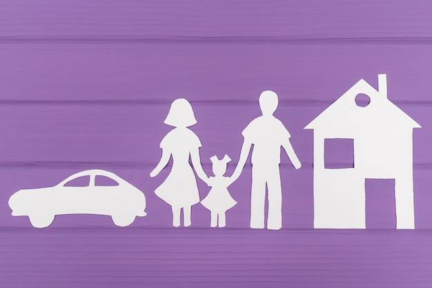 De silhouetten zijn uit papier gesneden van man en vrouw met een meisje bij het huis en de auto Premium Foto