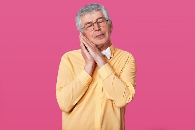 De slaperige grijze haired volwassen mens draagt geel overhemd met vlinderdas stelt met handen samen terwijl status met gesloten ogen op roze muur. man met kort kapsel wil slecht worden. mensen concept. Gratis Foto