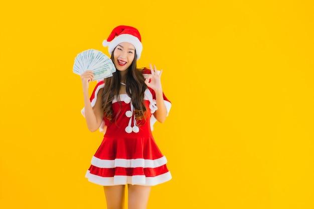 De slijtage van de portret mooie jonge aziatische vrouw kerstmiskleren en hoed met contant geld Gratis Foto