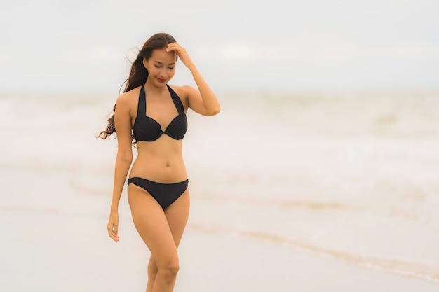De slijtagebikini van de portret mooie jonge aziatische vrouw op de strand overzeese oceaan Gratis Foto