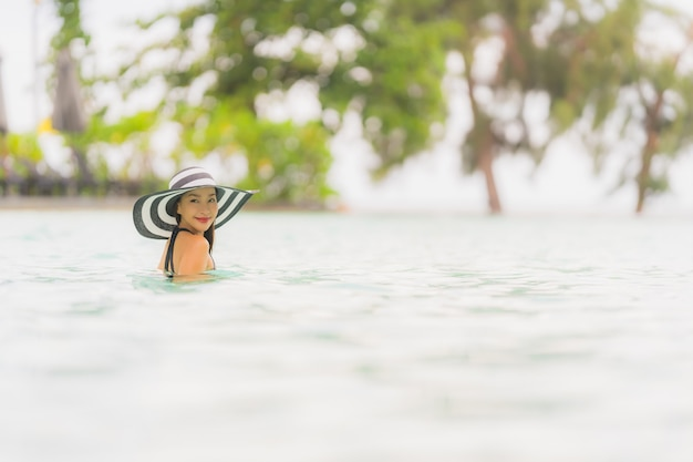 De slijtagebikini van de portret mooie jonge aziatische vrouw rond zwembad in hoteltoevlucht bijna overzees oceaanstrand Gratis Foto