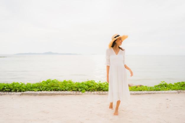 De slijtagehoed van de portret mooie aziatische vrouw met glimlach gelukkige vrije tijd op het strand en het overzees in vakantievakantie Gratis Foto