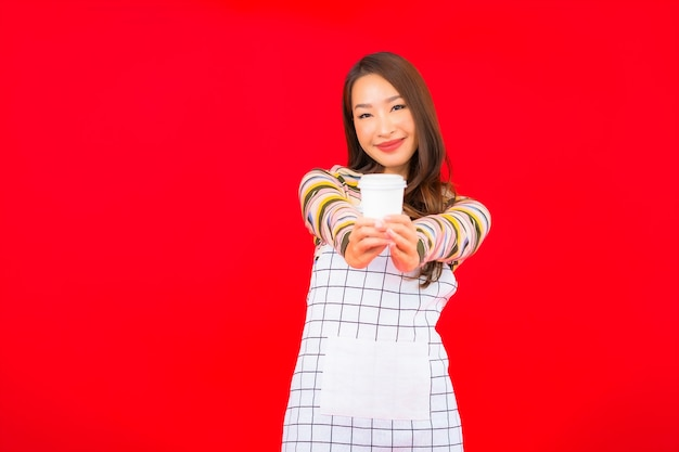 De slijtageschort van de portret mooie jonge aziatische vrouw met koffiekop op rode muur Gratis Foto