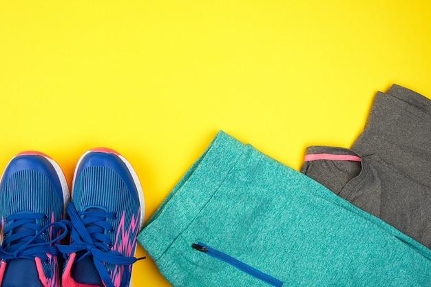 De sneakers en de kleding van blauwe vrouwen voor sporten op een gele achtergrond Premium Foto