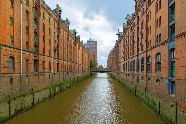 De speicherstadt is beroemd oriëntatiepunt van stad hamburg in duitsland. het is het grootste magazijndistrict ter wereld. rode bakstenen gebouwen staan op houten palen. Premium Foto