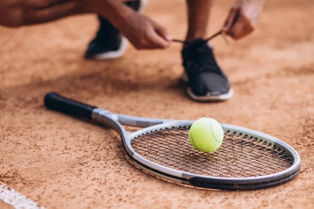 De speler van het jonge mensentennis bij het hof, dichte omhooggaand van de tennisracket Gratis Foto