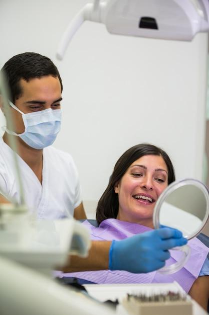 De spiegel van de tandartsholding voor patiënt Gratis Foto