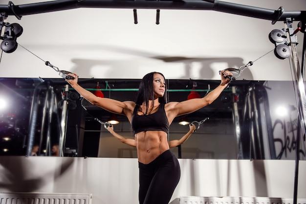 De spieren van de vrouwenverbuiging op kabelmachine in gymnastiek Premium Foto